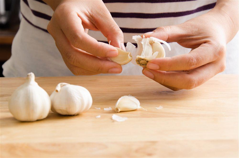 Hands peeling garlic cloves
