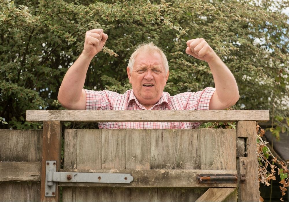 man-shaking-fist-over-garden-fence