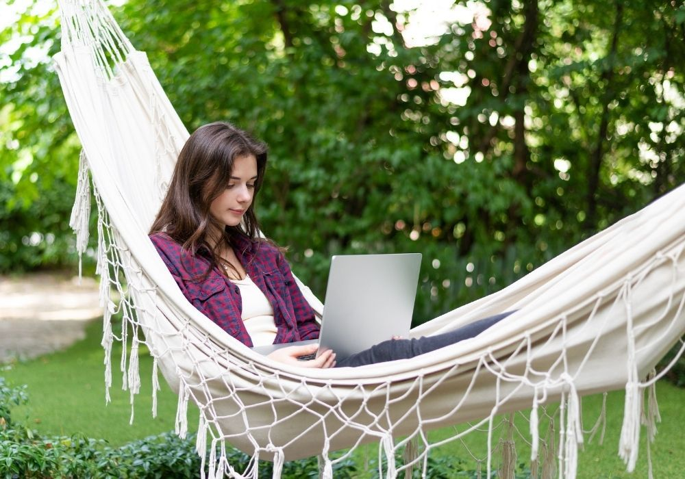 woman-with-laptop-in-a-hammock-in-garden