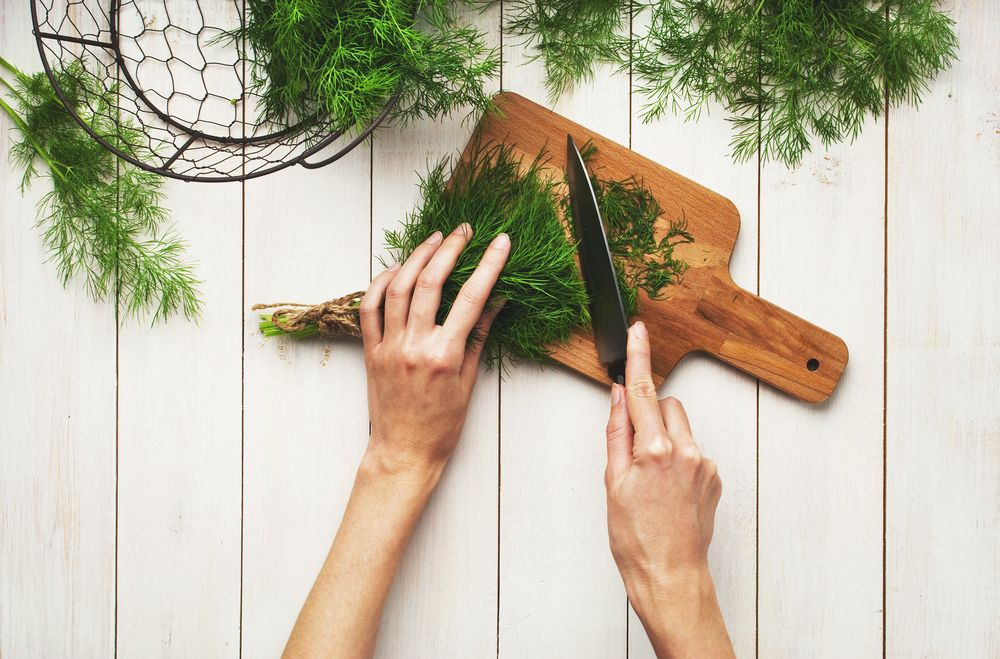 Woman chopping dill leaves
